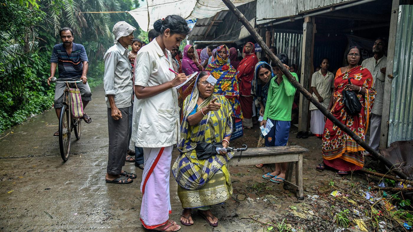 En kvinna får sina ögon undersökta av sjukvårdspersonal utomhus under en undersökning i Indien.