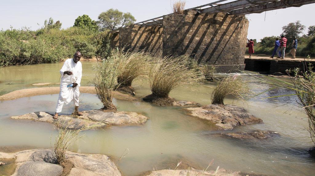 A man in Nigeria fishes in a river.