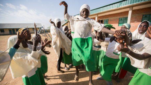 Barn på en skola firar att vi nådde en miljard behandlingar mot försummade tropiska sjukdomar.