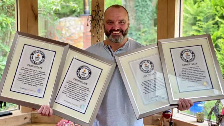 Lee Spencer håller upp sina certifikat från Guinness rekordbok.