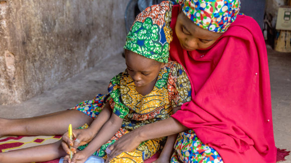 A mother helps her daughter with some school work.
