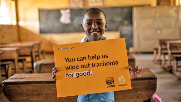 """Peace håller en skylt där det står """"Du kan hjälpa oss att eliminera trakom för gott""""."""