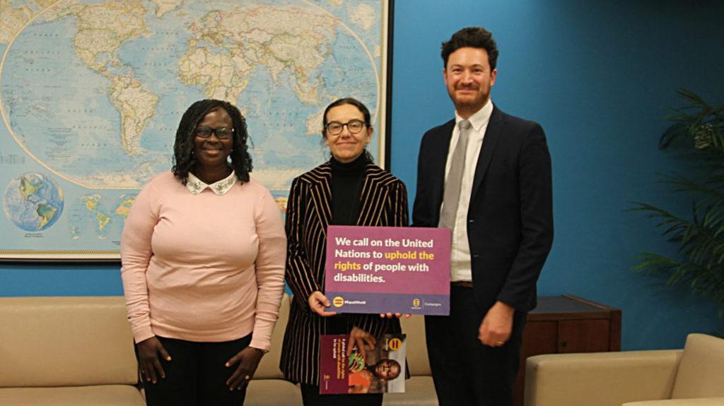 """Personal från Sightsavers håller upp en skylt i FN där det står """"Vi uppmanar Förenta Nationerna att upprätthålla rättigheterna för personer med funktionsnedsättning""""."""