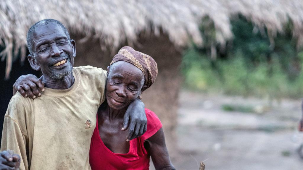 Gordane och Suhura håller om varandra och ler utanför sitt hem i Moçambique.