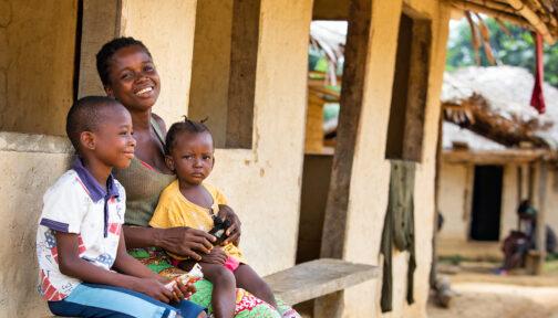 Sia och hennes barn ler efter en ögonundersökning i Liberia.