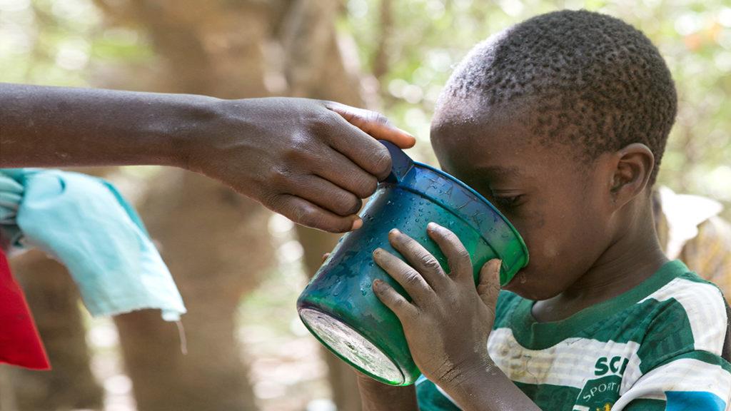 Ett barn dricker vatten ur en mugg under en kampanj för distribution av läkemedel i Nigeria.