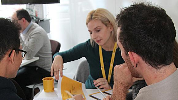 En grupp kreativa personer sitter vid ett bord och diskuterar sin uppgift.