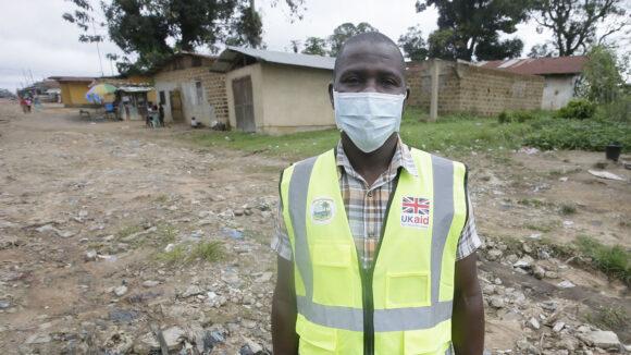 En man med munskydd står på en grusplan med hus i bakgrunden.