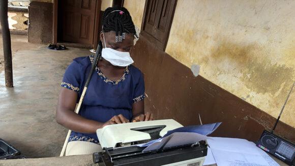 En flicka med munskydd använder en skrivmaskin.